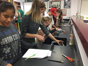 High school and 3rd grade students learn about science in a classroom