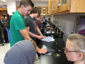 High school and 3rd grade students learn about science together in a classroom