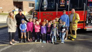 Elementary students pose with teachers and a firefighter in front of a Knox Volunteer Fire Department truck