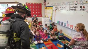 Firefighters speak to a class of pre-K students about fire safety.