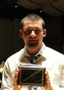 Neale Dunston stands with his Outstanding Student Award for Welding II