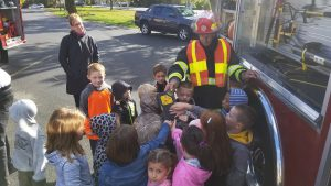 A firefighter from the Westerlo Volunteer Fire Company shows elementary students a piece of firefighting equipment.