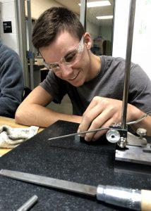 boy in safety goggles working on machine