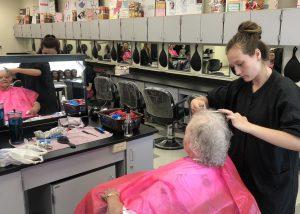 girl cutting woman's hair