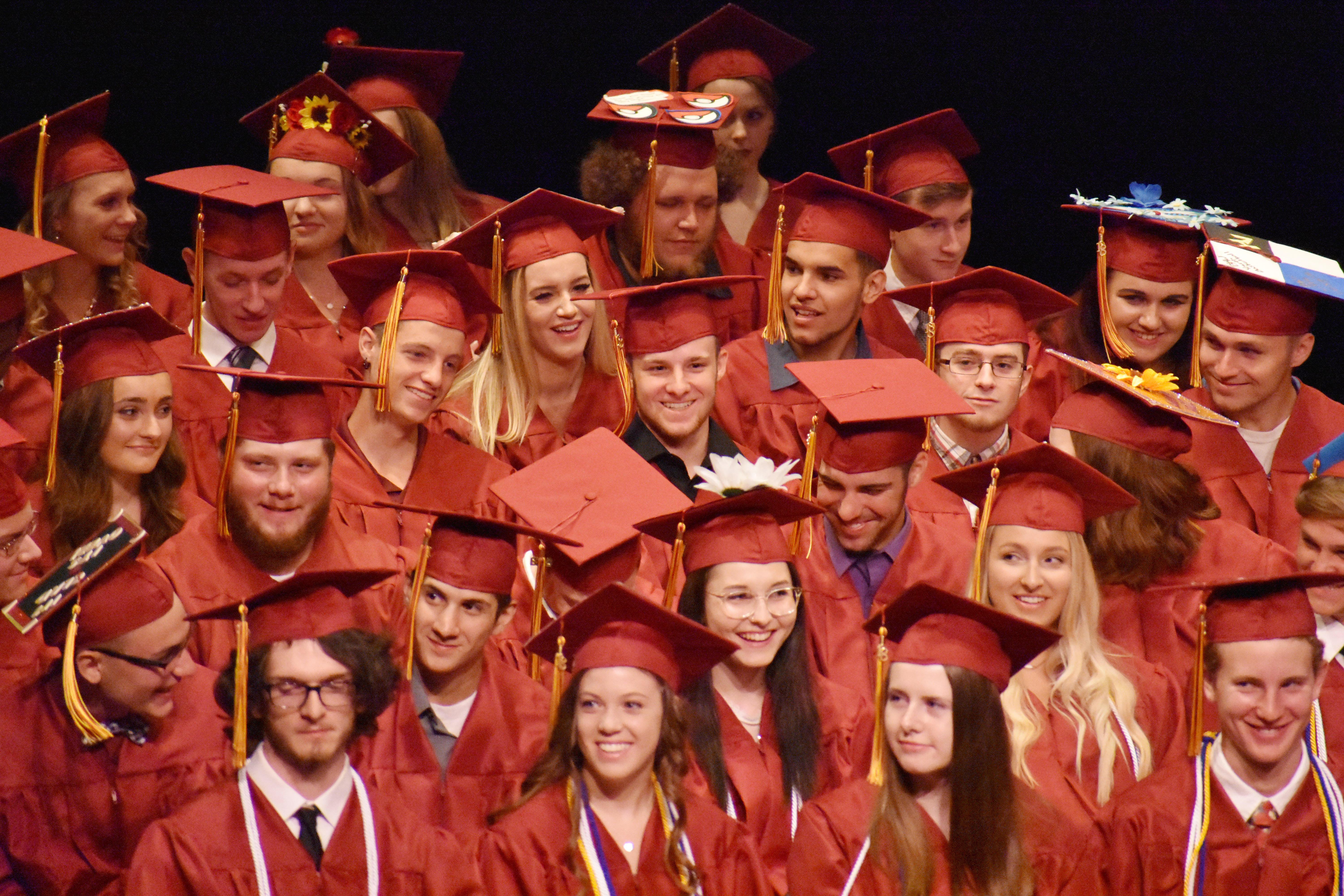 large group of graduates in their red caps and gowns