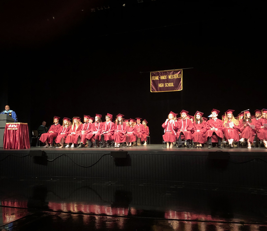 graduates on stage with a speaker