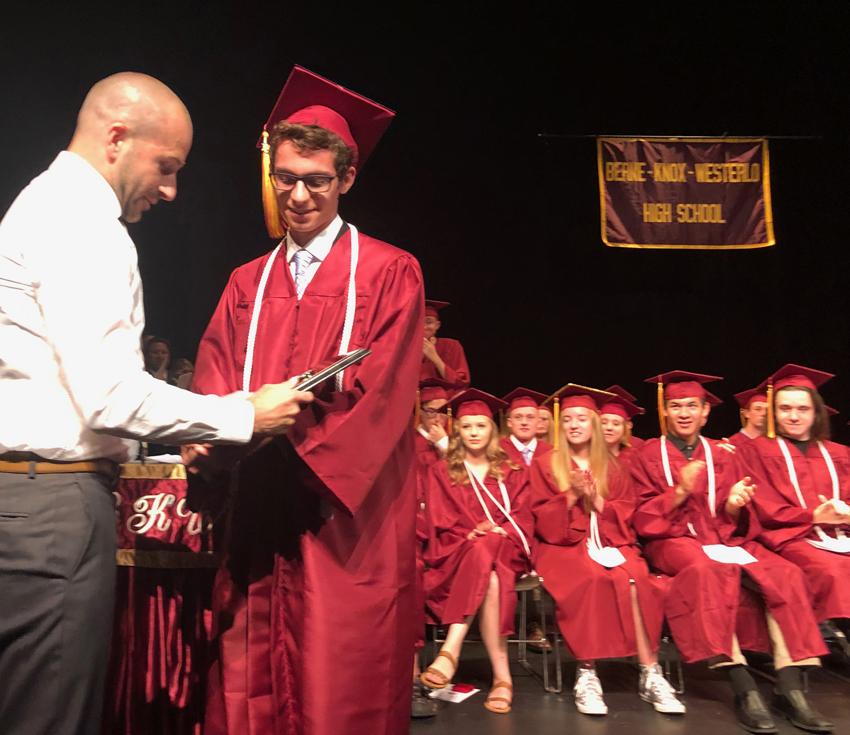 graduate presents an award to teacher