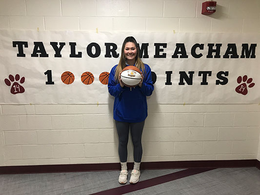 Taylor Meacham holding basketball in front of banner