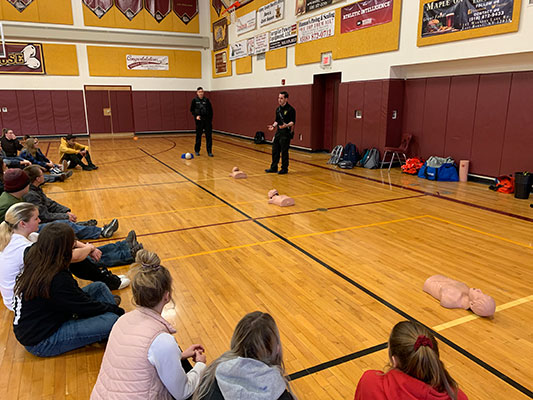 students sit and learn about CPR