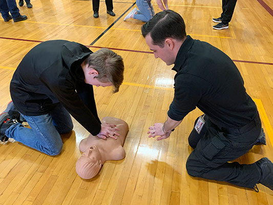 student performs CPR as Shift Supervisor Barach offers guidance