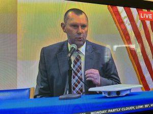 man in suit speaks on TV