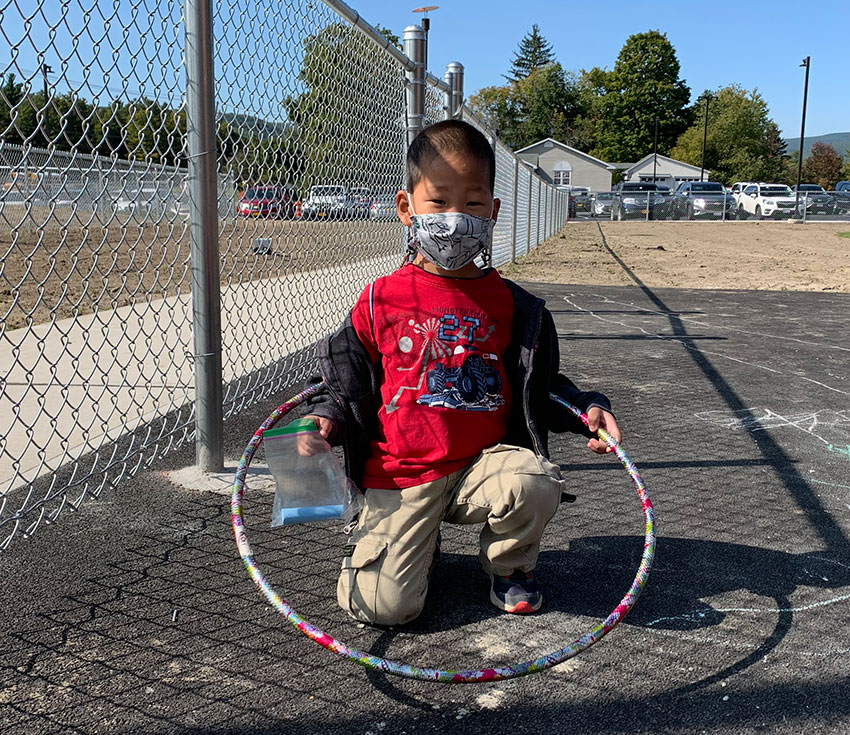 student holding hula hoop and chalk