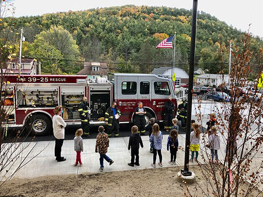 Elementary students listen as firefighters talk along side their truck