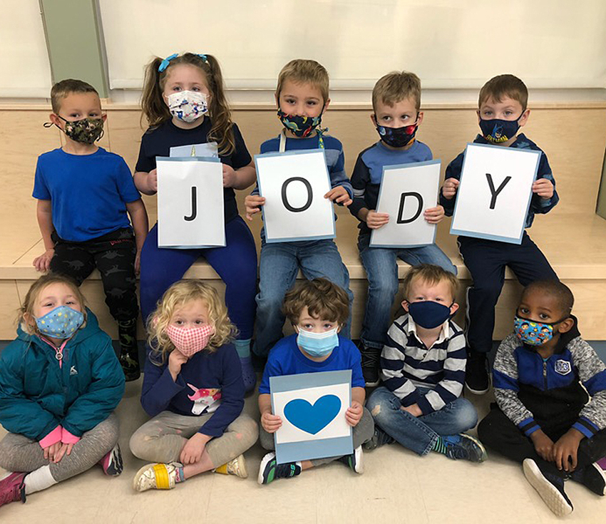 students wearing blue clothing and holding letters spelling out Jody