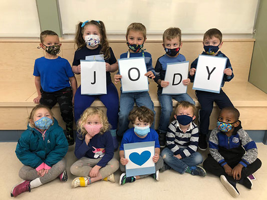 students wearing blue and holding cards that spell out Jody