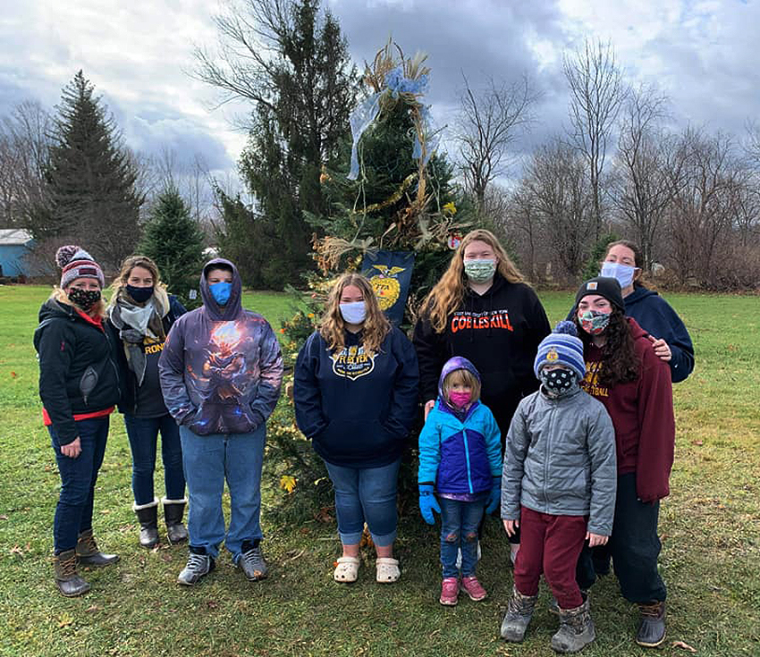 FFA members stand in front of tree they decorated