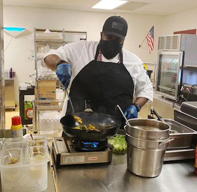Mr. Clark stirring food in a wok