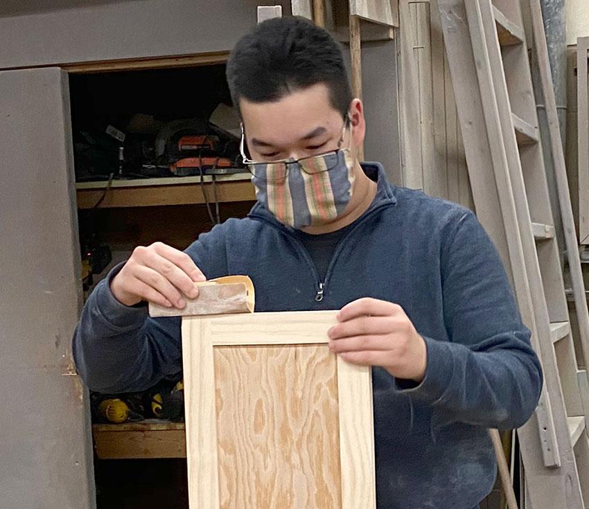 student sanding wooden board