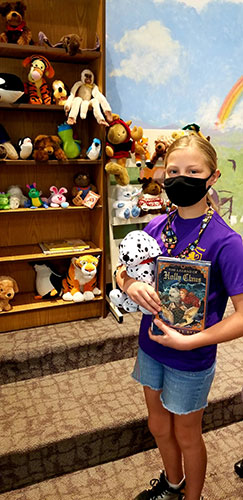 student holding library book and stuffed animal