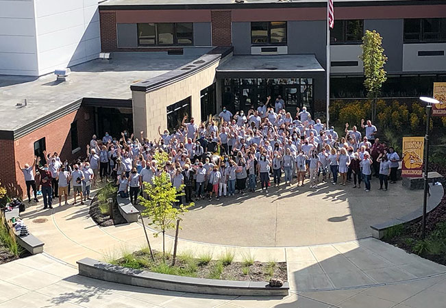 BKW faculty and staff standing as a group outside school building