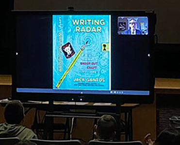 Jack Gantos and image that says Writing Radar on video screen in front of seated students